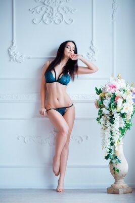 Affisch Ung, sexig kvinna med varma kropp poserar i underkläder på lyxig interiör nära blommor.