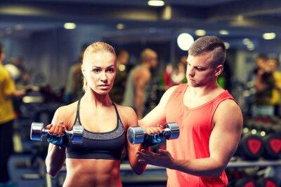 Affisch ungt par med hantlar musklerna i gymmet