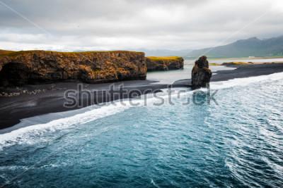Affisch Utsikt på Kirkjufjara strand och Arnardrangur klippa. Platser Myrdal, Atlanten nära Vik by, Island, Europa. Scenisk bild av fantastiskt naturlandskap. Upptäck jordens skönhet.