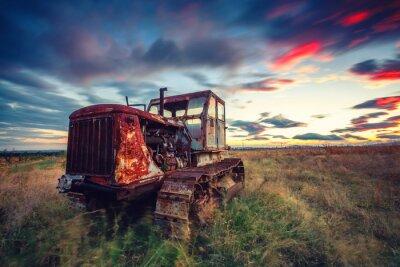 Affisch Vacker solnedgång över fältet och gamla rostiga traktor