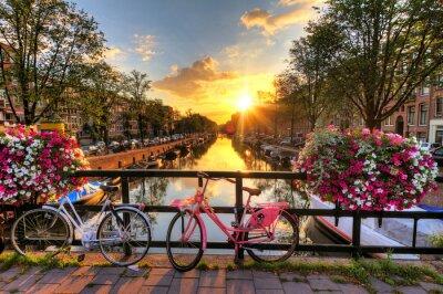 Affisch Vackra soluppgången över Amsterdam, Nederländerna, med blommor och cyklar på bryggan under våren