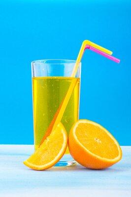 Canvastavlor apelsinjuice i ett glas med färgade sugrör och apelsinskivor på en blå bakgrund