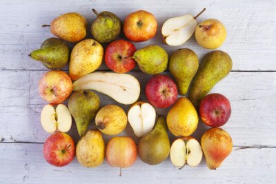 Canvastavlor äpplen och päron helhet och halverad skott från ovan på vita brädor
