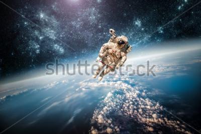 Canvastavlor Astronaut i yttre rymden mot bakgrund av planeten jorden. Element av den här bilden möblerad av NASA.