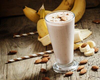 Canvastavlor Banan smoothie med mjölk, mald mandel i en stor kopp på
