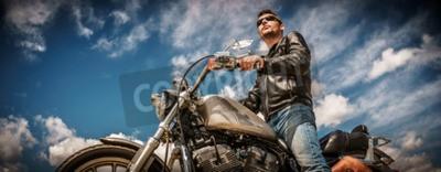 Canvastavlor Biker man som bär en läderjacka och solglasögon som sitter på sin motorcykel.