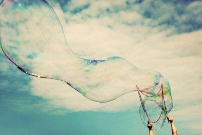 Canvastavlor Blåsa stora såpbubblor i luften. Tappning frihet, sommarkoncept.