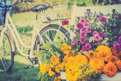 Canvastavlor Blombukett på en vit stol. Suddig retro cykel i bakgrunden.