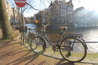 Canvastavlor Cyklar som kantar en bro över kanalerna i Amsterdam, Nederländerna