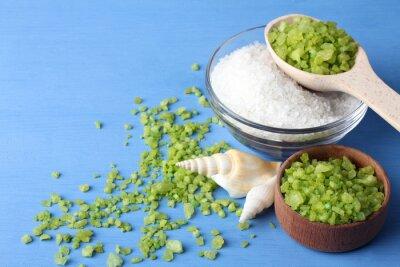 Canvastavlor doftande grön och vit havssalt är i en glasskål och trä bowl.Scattered runt green havssalt med snäckskal på en blå träbord med snäckskal