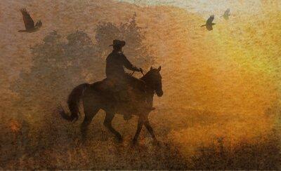 Canvastavlor En dramatisk design av en cowboy och hans ridning på en äng i solnedgången med kråkor flyger över. En blandad massmedia konstverk i fotografi och akvarell.
