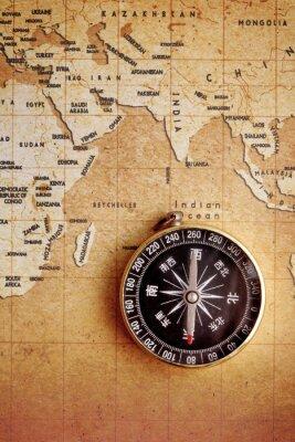 Canvastavlor En gammal mässing kompass på en skattkarta bakgrund