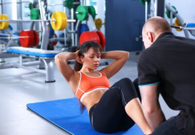 Canvastavlor En ung kvinna med sin tränare på gymmet