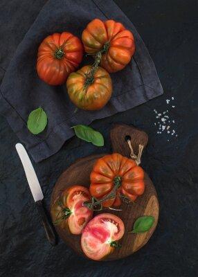 Canvastavlor Färska mogna hairloom tomater och basilika på rustik träskiva över svart sten bakgrund.