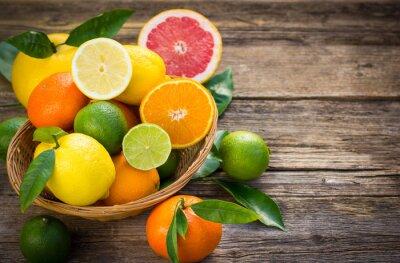 Canvastavlor Färska och saftiga citrusfrukter i korgen på den rustika bord