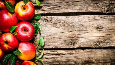 Canvastavlor Färska röda äpplen med gröna blad på träbord.