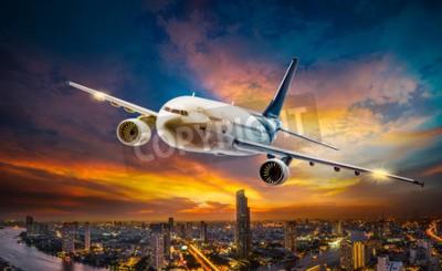 Canvastavlor Flygplan för transport som flyger över nattscenen staden på vacker solnedgångsbakgrund