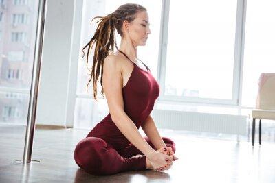 Canvastavlor Fokuserad vacker kvinna gör yoga i studio
