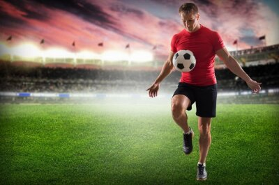 Canvastavlor Fotboll. Professionell fotbollsspelare sparkar boll