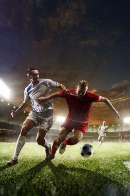 Canvastavlor Fotbollsspelare i aktion på solnedgången stadion bakgrund