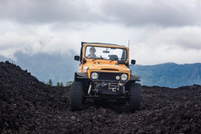 Canvastavlor Frontside syn på en lockig hård chaufför i yelow offroad fordon parkerad på toppen av en dal med vulkaniska berg och berg i Bali, Indonesien