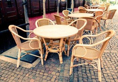 Canvastavlor Gatuvy över en kaffe terrass med bord och stolar