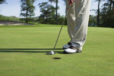 Canvastavlor Golfspelare kranar in med putter på grönt med träd nära en sjö