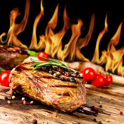Canvastavlor Grillat nötkött biffar med lågor på bakgrund