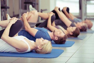 Canvastavlor grupp gör stretchövningar i gymmet