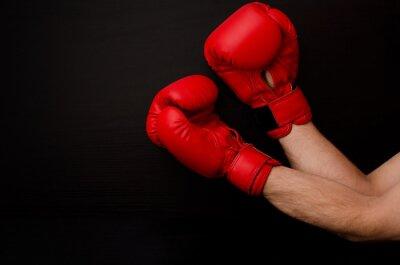 Canvastavlor Hand i röda boxhandskar i hörnet av ramen på en svart bakgrund, tomrum