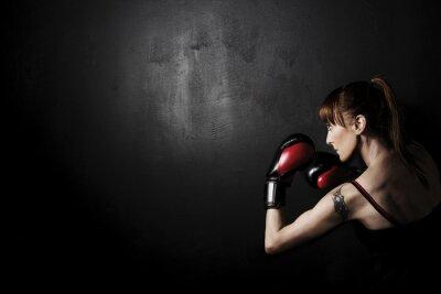 Canvastavlor Kvinna boxare med röda handskar på svart bakgrund, hög kontrast med desaturated grunge filter i studio