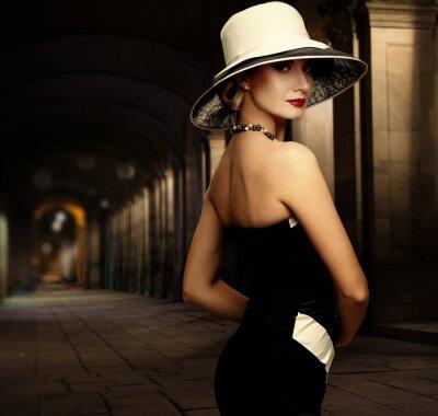 Canvastavlor Kvinna i svart klänning och stor vit hatt ensam utomhus på natten