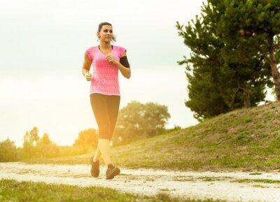 Canvastavlor Kvinna Running Country på vackra solnedgången.