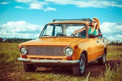 Canvastavlor Kvinnan driver en gammal gul bil. Landsbygd bakgrund.