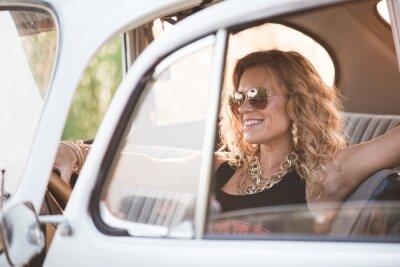 Canvastavlor Lycklig, sorglös kvinna njuta av en retro bil, varm sommardag.