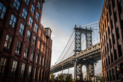 Canvastavlor Manhattan Bridge sedd från en smal gränd omges av två tegelbyggnader på en solig dag på sommaren