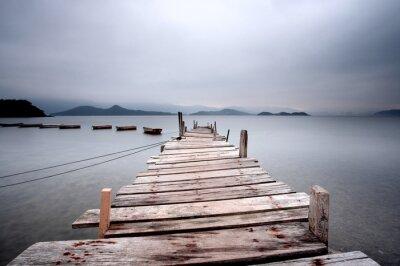 Canvastavlor Med utsikt över en brygga och en båt, mörk ton.