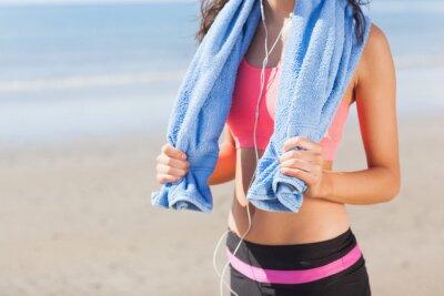 Canvastavlor Mitten delen av frisk kvinna med handduk runt halsen på stranden