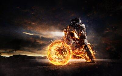 Canvastavlor Mörk motorbiker håller på brinnande motorcykel i solnedgångsljus