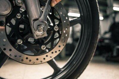 Canvastavlor Närbild på mans hand med monteringsnyckel nära motorcykelens fordon.