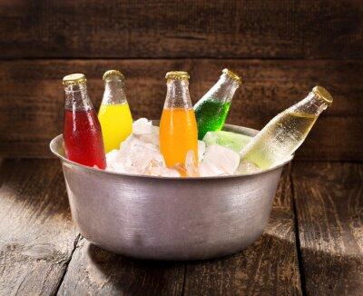 Canvastavlor olika flaskor av läsk i hinken med is