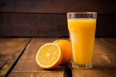 Canvastavlor Orange frukt och glas juice på brun trä bakgrund