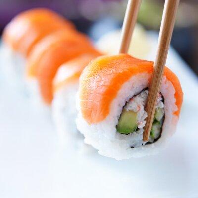 Canvastavlor plocka upp en bit av sushi med pinnar