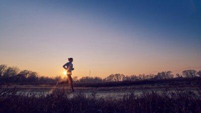 Canvastavlor ragazza atletica si allena all'aperto su terra di sera