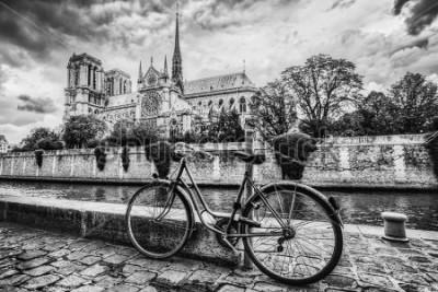 Canvastavlor Retro cykel bredvid Notre Dame-katedralen i Paris, Frankrike och floden Seine. Svartvit tappning