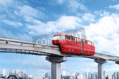 Canvastavlor Röd monorail tåg mot blå himmel och modern stad i bakgrunden