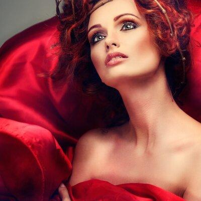 Canvastavlor Röda hår. Porträtt av vacker flicka i rött tyg