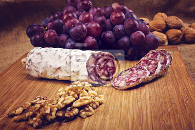 Canvastavlor salami med nötter på en trä platta med druvor