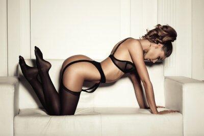 Canvastavlor sexig kvinna i förförisk svart underkläder sitter på en soffa i sto