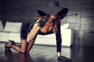 Canvastavlor Sexig kvinna i hatt och piska på knä på golvet inomhus